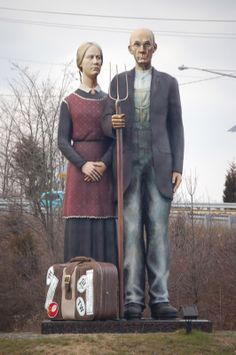 'God Bless America' - a 25 foot tall statue by Seward Johnson in Hamilton, NJ;  based on the famous painting 'American Gothic' by Grant Wood in 1939;  ...Mr. Johnson has taken the liberty of adding a suitcase with destination stickers prominently displayed. Some folks look at this as indicative of the USA being a nation of immigrants, while others say it shows the penchant for travel among Americans.