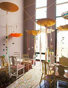 Such a whimsical wedding scene - thrift store umbrellas, confetti garlands, mismatched chairs