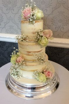 3 tier semi naked cake decorated with fresh avalanche and sweet avalanche roses and gypsophilia