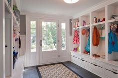 Large mud room with built-in beadboard lined mud room lockers over storage benches on either side of the glass paned back door with sidelights over a slate tiled floor layered with an interlocking circled patterned black and tan rug runner.