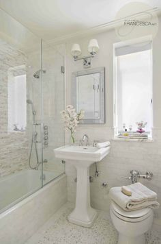 Marble and porcelain make a small bathroom a dream in white.