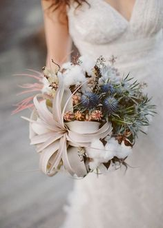 We're swooing over this organic wedding bouquet with air plants, blue thistles, and cotton