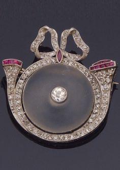 An Art Deco platinum, rock crystal, diamond and ruby brooch.