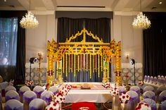 Wedding Mandap; Red carpet and Floral arrangement lining the walkway at an indoor wedding
