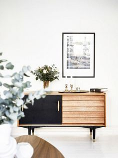 Wood and black console table with framed poster