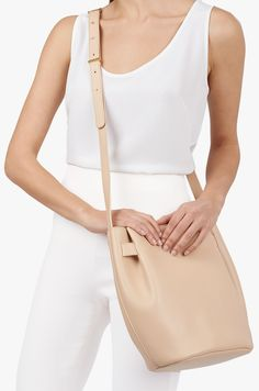 Spring's clean, architectural approach lends a more structured stance to our signature cinch bag silhouette. Its reinforced smooth leather reveals a sleek look and divine details like perfectly pleated sides and a concealed magnetic closure. It is crafted in Italy from the finest full-grain Italian leather with an adjustable strap that transitions from shoulder bag to crossbody with effortless polished gold studs. Opt to add a tonal tassel to the mix for an elevated accent.