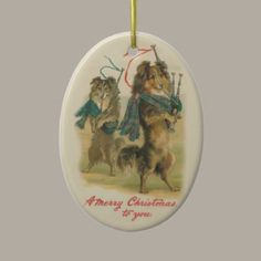 """Vintage Christmas Ornament  This Christmas ornaments features a lovely vintage Christmas image of a pair of Collie dogs playing bagpipes. The caption reads, """"A Merry Christmas to You"""". Obviously for Scottish dog lovers! Lovely oval Christmas ornament that is ready to hang."""