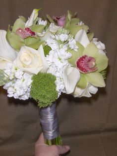 Bride's bouquet with calla lily, stock, orchids, roses and trachelium. Wrapped with silver ribbon.