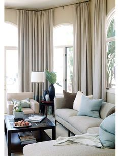 The ceiling to floor curtains make the room cozy and relaxing. Love the soft neutral colors. Accented with the ocean sky blue. Beautiful.