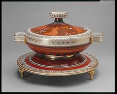 """1787 Italian (Naples) Soup tureen in the Royal Collection, UK - From the curators' comments: """"Soft paste and tin glazed porcelain large circular tureen with strap handles, cover with a flat circular knop and socle foot, all on a stand on four gadrooned and tapering legs. Brown ground with a white and gilded anthemion border and orange classical figure scene."""""""