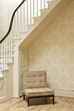 Underside of stairs in Farrow & Ball's Matchstick with Lotus BP 2003 wallpaper pattern on wall.
