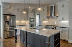 I like this. Island is functional to eat at. Cabinets go all the way up. Subway tiles. Dark island cabinetry.
