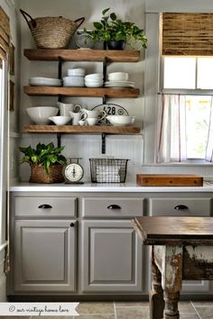 Stile rustico dosato sapientemente nel colore: il grigio tortora chiaro abbinato al legno delle mensole e al tavolo antico.