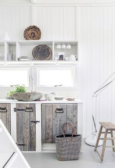 The rough, rustic wood doors on the cabinets in this summer cottage kitchen give the room a unique personality.