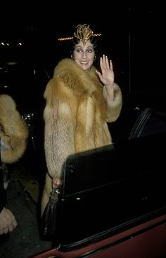 cher wearing fur | Cher wears an interesting headdress with this large fur coat.