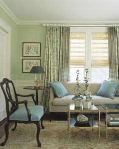 Green.  The curtains pair a plaid with a toile; the shade of green on each is strong, but it's used like line work on a cream ground, softening the effect. A pale mint coats the walls, and a darker hue appears on the tole lampshade and hollyhocks on the coffee table.