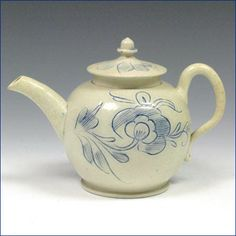 """A saltglaze teapot with acorn knob, with scratch blue decoration of a large scrolling flower. Ht: 3.7"""", 9.5 cm c.1750-60 Ref: G. Wills, English Pottery and Porcelain, fig. 80 for a similar teapot inscribed and dated 1760."""
