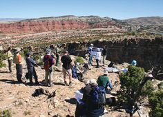 'World-Class Exposures' Offered in ACE Field Trips - Field trip participants discussing reservoir development in the Tensleep Sandstone at Alcova Reservoir in Wyoming. Photo by Peter Henning