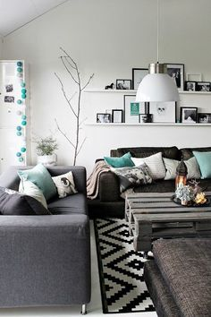 This modern and chic living room design is gorgeous. The charcoal and teal colour combination is clean and fresh