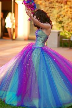 I'm all for white dresses, red dresses, blue dresses, purple dresses, but ZOMG I actually gasped out loud when I saw this picture of Kelly Devoto's fantastical colorful peacock-y wedding dress -- which it turns out was actually designed to be a prom dress.