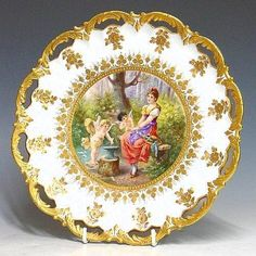 Late 19th C. Bavarian Cabinet Plate, the painted centre with young maiden seated in woodland with cupids making arrows, framed by elaborate formal and jewelled gilding with similar gilded flower sprays and pierced scroll rim, 9.5in