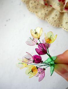 Květinovka... Náušničky zdobí kvítky a lístky z barevných průhledných plastických hmot, stonky květinek tvoří zelené nylonové lanko. Mechanický náušnicový háček z obecného kovu - úprava platina.