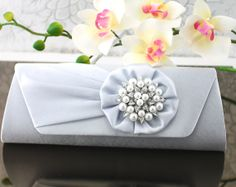 """Wedding Clutch Wedding Purse Bridal Clutch by goddessdesignsgems, $59.00 """"Classic Elegance"""" this gorgeous satin clutch in a shimmering silver color features a pleated front flap with a tufted satin flower embellished with a stunning crystal & white pearl brooch creating a very rich & elegant look. Magnetic clasp closure under the front flap easily secures items inside."""
