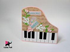 Postal  de Parabéns em forma de piano (versão cor-de-rosa), construído através da aplicação de diferentes elementos de papel assumindo um estilo vintage. No postal é visível pequenas borboletas, flores e 4 ramos de folhas (verdes e brancas). A mensagem é inserida no verso do postal.