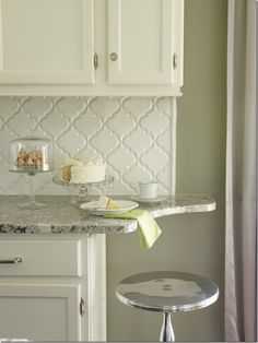arabesque backsplash. Cute little overhang for a stool in a compact kitchen, though the upper should stop even with the lower and just extend the counter. Backsplash could even extend and wrap up the wall along the side of the upper all the way to the ceiling.