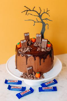 """Top a chocolate cake with chocolate ganache, letting it drip down the sides. Pipe """"RIP"""" onto fun size Crunch Bars to create gravestones. Crush up additional Crunch bars to use as """"dirt"""" alongside Buncha Crunch pieces. Place gravestones atop your cake and add crushed up bars and Buncha Crunch around each one. Add candy pumpkins or other edible adornments as desired. Complete the cake by cutting a spooky tree shape out of black paper. Tape to a bamboo skewer and place it behind the gravestones! Halloween Desserts, Halloween Cakes, Halloween Party, Candy App, Graveyard Cake, Fun Size, Paper Tape, Cupcake Cakes, Cupcakes"""