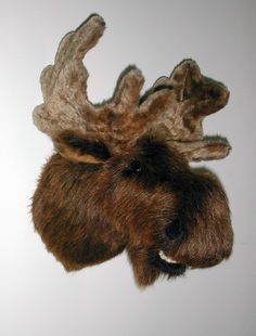 "Plush Moose Head ""Mitch"" Large Shoulder Mount. Not too big and not too small. Mitch has deep fuzzy nostrils and a lower jaw. His nose is a little broader, and the bridge between his eyes is just the right size for wearing sunglasses. His antlers are plush fur fabric. PRODUCT SPECS: Ready to hang. Mitch's depth is 15"" from nose to wall. Adjustable antler span is 18"". Girth at shoulder is 25""."
