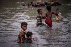 Rohingja gyerekek kelnek át a Naf-folyó egyik sekélyebb szakaszánál.