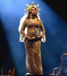 Twinning: Beyonce cradled her bump while onstage while standing on a pedestal...