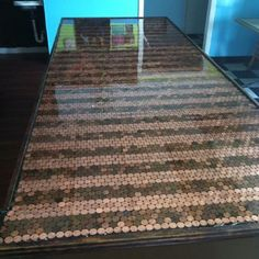 """Pinner said: """"Penny lined counter top project. We took our plain counter in our restaurant and glued penny's to the top and poured an epoxy finish. It's striped with new penny's and old penny's. A+ in crafty department for my husband. He's so talented."""""""