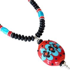 Southwestern Lampwork Glass and Jet Necklace Add a splash of color to any outfit with this festive, lampwork glass and Jet necklace. Red, bright turquoise and jet black create a classic southwest design. Jet freeform beads and sterling silver bead caps and spacers create a classic look. The necklace measures 18 inches with a hook clasp. It can be extended to 21 inches with an extender chain.