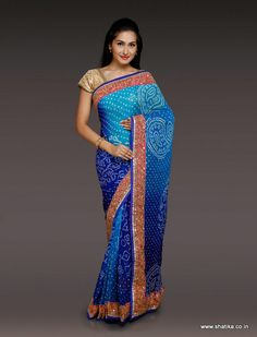 A pure crape chiffon fabric evocatively dyed in evident shades of blue enhances the beauty of Phullara Blue Pure Bandhej Saree that showcases dots, paisley and bel design imprinted on it in the traditional tie and dye process of Bandhej. The traditional gottapatti is contrasting color is an attention grabber.