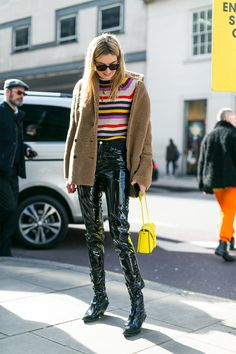 Multi-color striped sweater, beige jacket and black leather pants and boots.
