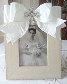 "CLICK PIC TO BUY! ""Fancy Cross"" Ivory 5x7 Frame-Double Ivory Ribbon and Stunning Rhinestone Cross make this frame worthy of your most special memories. Custom orders let you choose frame, ribbon and brooch style. Click on the pic to see the cross up close. $98.00 www.nobleniches.com #wedding #baptism #Christening #firstcommunion #bridalshower #babyshower #pictureframe #weddinggiftideas #babygiftideas #anniversary #nobleniches #minthill #minthillgift #charlotteboutique #homestylesgallery…"