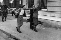Robert Capa Paris August 25th, 1944   After the entry of the French 2nd Armored Division, numerous pockets of German snipers had to be rooted out in street fighting. Many French civilians and members of the Resistance helped the French troops in this fighting. This photograph shows a French civilian who was unable to contain his wrath against a German soldier who had surrendered.