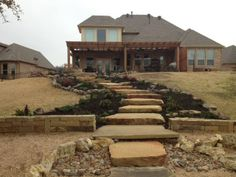An entry sidewalk made of large, flat top stones bordered on each side by xeriscaping which is in turn bordered by large rocks. Landscape Photos, Landscape Design, Garden Design, Landscaping Company, Garden Landscaping, Flower Bed Edging, Entry Stairs, Landscape Services, Outdoor Living Areas