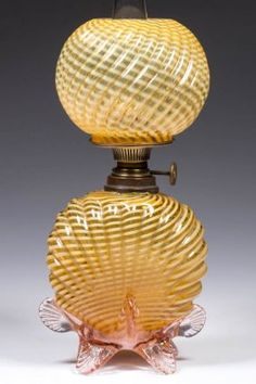 """EXTREMELY RARE EMBOSSED REVERSE SWIRL ART GLASS; amber opalescent, embossed shell base with applied pink glass feet and rigaree, matching pattern ball shade; period burner shade ring and chimney. Fourth quarter 19th/early 20th century. 8 1/2"""" H to top of shade, base 4 3/4"""" to top of collar. / SOLD $1,400"""