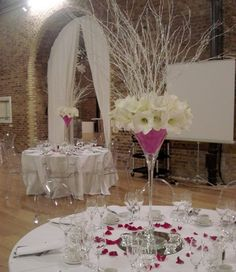 Wedding Flowers Individual blooms of traditional white gladiolius are given a contemporary twist by layering them in a martini glass style vase filled with vibrant pink sisal and a sparkly centerpiece of glittering white twigs. A tall glamorous eye-catching  centerpiece for a modern wedding celebration.