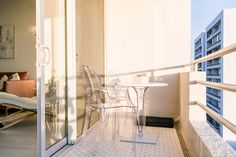 On the balcony, the Ice Round Bistro Table is from Compamia and the Clear Accent chairs are by Fine Mod Imports.