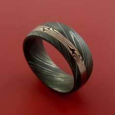 This 7mm wide DAMASCUS ring has a 2mm Off Center groove, inlaid with a deep 14K ROSE GOLD and SHAKUDO a gold/copper alloy) that is twisted