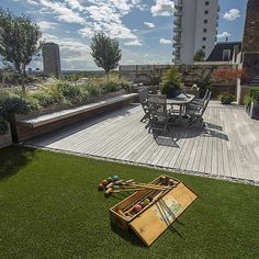 Roof terrace with decking, artificial level lawn and LED lighting design at New Concordia Wharf