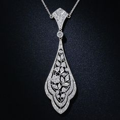 This alluring circa 1910 pendant necklace is a breathtaking blend of early Art Deco design elements and the divine couture lace of the Edwardian platinumsmiths. Nearly two carats of bright-white, dazzling diamonds highlight beautifully wrought flowers and leafy vines in a curvilinear concentric frame. This enchanting pendant measures 2 3/4 inches long and just over 3/4 inch wide, suspended from an 18 inch long platinum cable chain with a secure clasp.