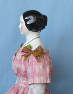 "German Antique china doll with braided bun stands between 22"" to 23"" tall. The doll's head is slightly pink-tinted; her eyes are grey which makes her"