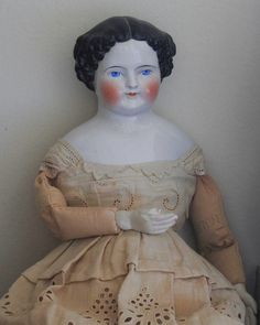 Vintage china head doll in original clothing.