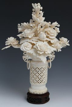 """CHINESE CARVED IVORY VASE WITH FLOWERS An elaborately carved Chinese ivory floral arrangement over pierced vase containing an assortment of flowers within. Vase has carved handles with rings. Attached to wooden base. Weight: 776g with base Size: 13.5"""" with base"""
