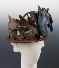 Hat ca. 1915, wool, feathers.   Mme. Pauline  (American) / Madame Pauline, a milliner located in Bedford-Stuyvesant area [of Brooklyn], makes a strong statement on the fascination with the use of birds and feathers. Not only is a full bird affixed to the front, but numerous bird wings are also applied all around to completely cover the sides of the crown.